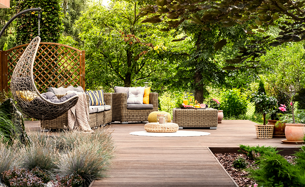 Beautiful wooden terrace with garden furniture surrounded by greenery