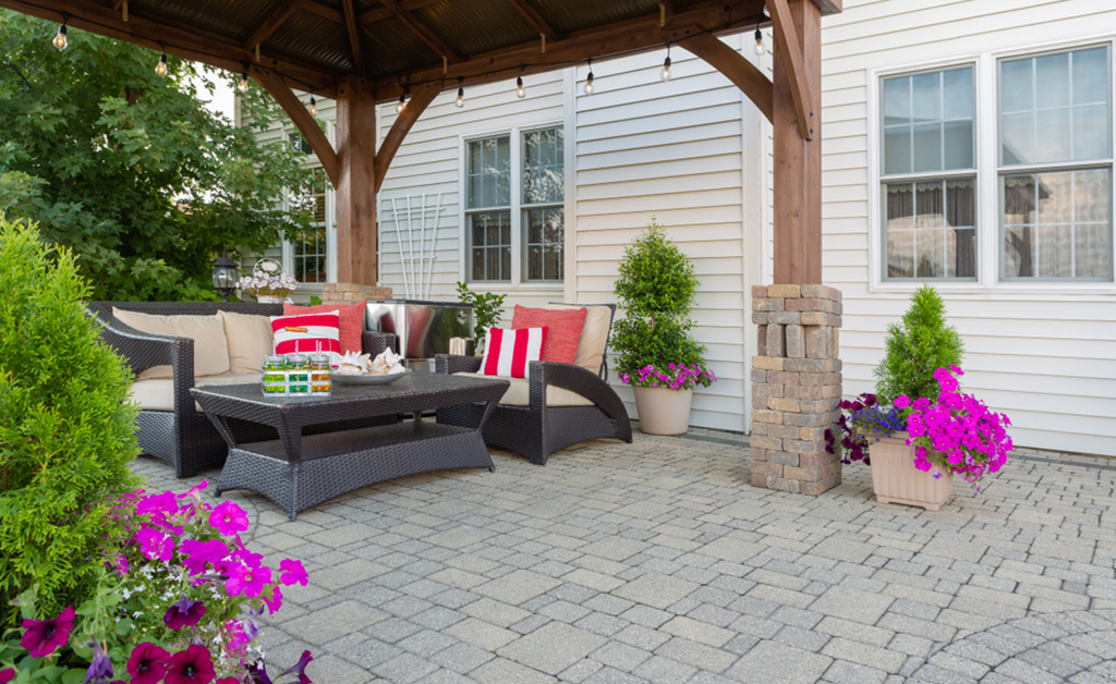 exterior patio and summer living space with a covered gazebo, colorful petunias and comfortable seating