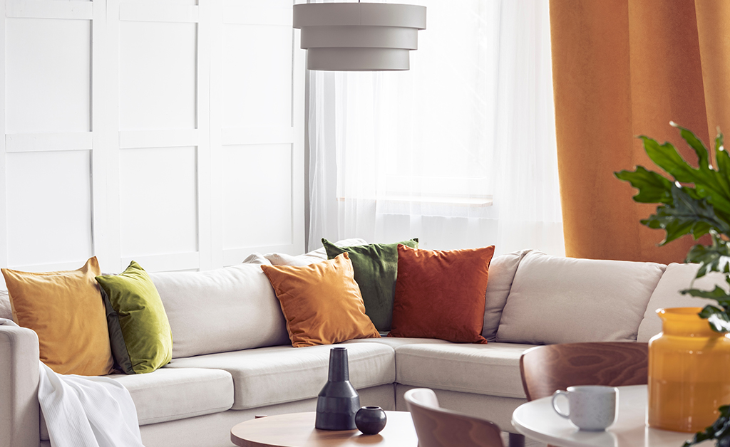 Living room with light couch and orange pillows and an orange curtain